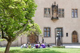A group of vsitors sitting in the courtyard of the Luther House / Augusteum